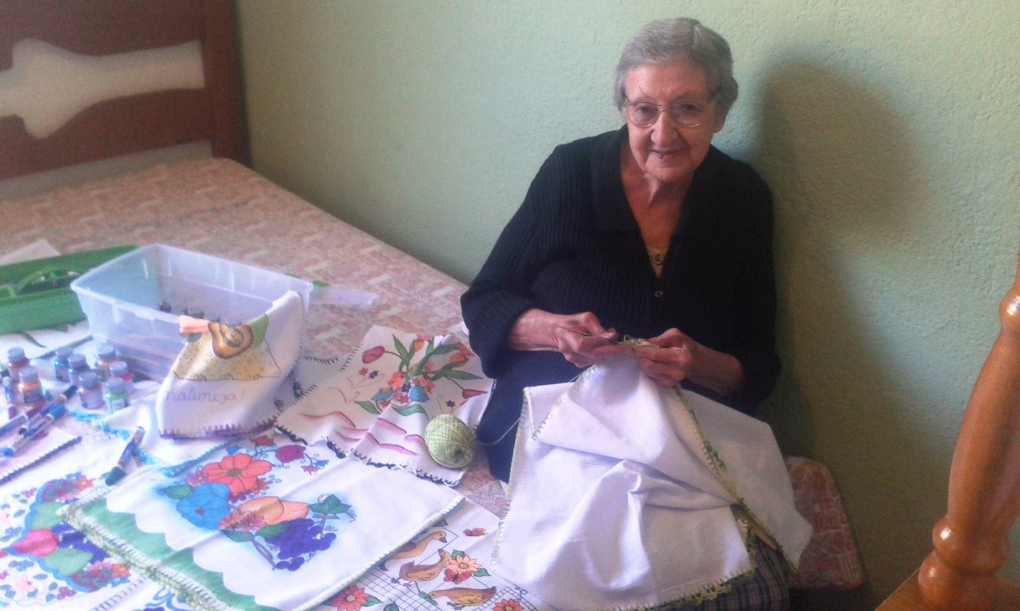 Dona Aparecida faz bicos ou barrados de crochê em cada um dos panos de prato; depois pinta e presenteia com eles os familiares